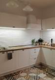 Biała drewniana żaluzja 25mm na oknie kuchennym narożnym. Styl skandynawski,