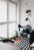 Biała drewniana żaluzja 25mm montowana inwazyjnie w świetle szyby na oknie balkonowym w salonie o stylu skandynawskim.