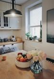 Biała drewniana żaluzja 25mm montowana inwazyjnie w świetle szyby (do listw przyszybowych) na oknie kuchennym z wywietrznikiem.