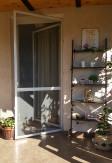 Aluminiowe drzwi moskitierowe na zawiasach samodomykających na tarasie w kolorze białym