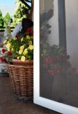 Moskitiera drzwiowa luminiowa na zawiasach samodomykających na tarasie w kolorze białym