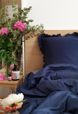 Elegancka oraz przytulna pościel z falbaną w kolorze ciemnym niebieskim 200x220 w jasnej sypialni