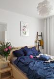 Elegancka oraz przytulna pościel z falbanką w kolorze ciemnym niebieskim 200x220 w jasnej skandynawskiej sypialni.