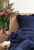 Elegancka oraz przytulna pościel z falbanką w kolorze ciemnym niebieskim 160x200 w jasnej skandynawskiej sypialni.