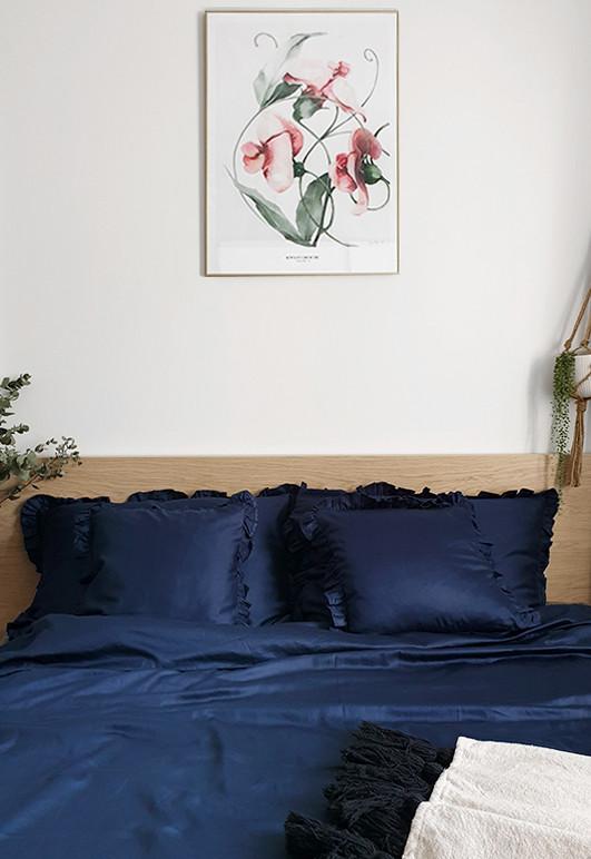Elegancka oraz przytulna pościel z falbanką w odcieniu głębokiego granatu o rozmiarze 160x200 w jasnej skandynawskiej sypialni.