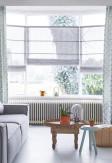 Szare rolety rzymskie o tkaninie transparentnej z ozdobnymi pionowymi paskami zamontowane w wykuszu salonu w stylu skandynawskim
