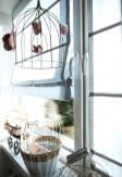 Roleta rzymska o gładkiej transparentnej tkaninie w kolorze szarym montowana bezinwazyjnie na ramie okiennej.