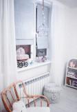 Roleta rzymska o gładkiej transparentnej tkaninie w kolorze szarym montowana bezinwazyjnie w pokoju dziecięcym.