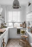 Biała drewniana żaluzja o lamelach 50mm z drabinką taśmową na dużym oknie kuchennym w jasnej kuchni.