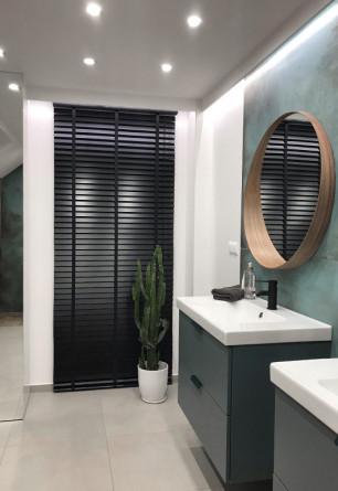 Żaluzja drewniana czarna 50mm z drabinką taśmową montowana na ścianie w łazience.