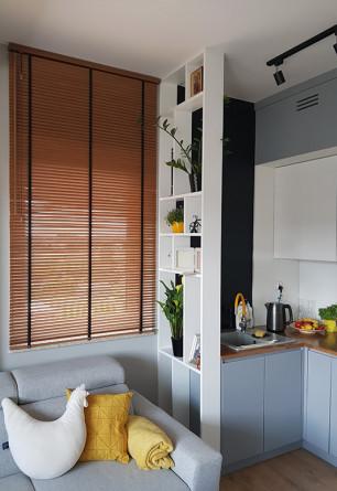 Żaluzja drewniana 25mm z drabinką taśmową w odcieniu dąb montowana do sufitu na oknie kuchennym.