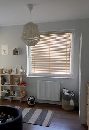 Żaluzja drewniana 25mm na w kolorze naturalnego drewna montowana na oknie z wywietrznikiem w pokoju dziecięcym.