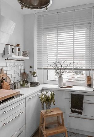 Biała żaluzja drewniana 50mm z drabinką taśmową montowana do sufitu w kuchni o stylu skandynawskim.