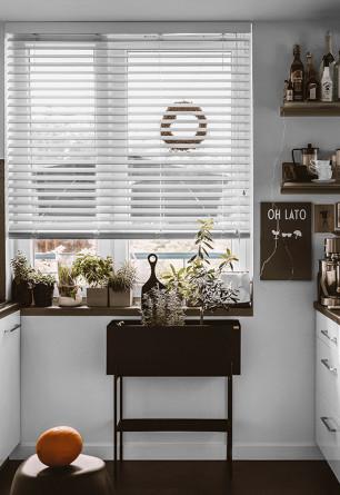 Biała żaluzja drewniana 50mm z drabinką taśmową montowana do sufitu nad oknem kuchennym.