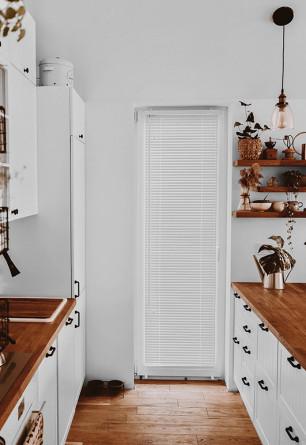 Biała żaluzja drewniana 25mm montowana bezinwazyjnie na skrzydle okiennym w kuchni o stylu skandynawskim.