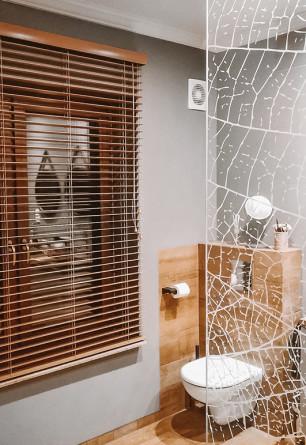 Żaluzja drewniana w kolorze kurkuma o lamelkach 50mm montowana na ścianie w łazience.
