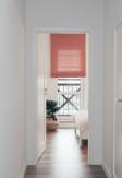 Roleta rzymska w odcieniu różu nad oknem balkonowym w nowoczesnej jasnej sypialni. Montaż do sufitu nad wnęką okienną.