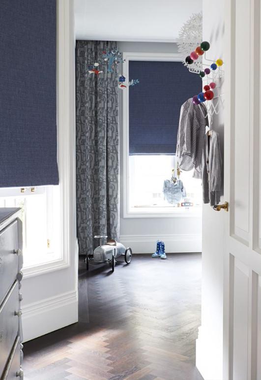 Niebieska roleta rzymska w pokoju małego chłopca. Montaż we wnęce okiennej.