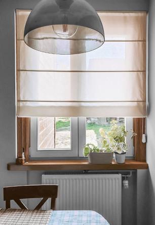 Roleta rzymska w tkaninie transparentnej w odcieniu beżowym montowana we wnęce okiennej.