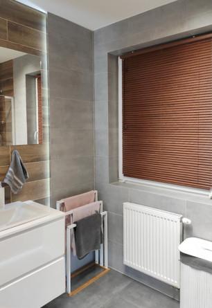 Żaluzja drewniana 25mm na wymiar w odcieniu złotego dębu montowane bezinwazyjnie na oknie w łazience.