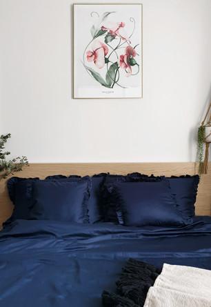 Elegancka oraz przytulna pościel z falbanką w odcieniu głębokiego granatu o rozmiarze 200x200 w jasnej skandynawskiej sypialni.