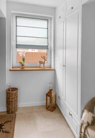 Roleta rzymska o gładkiej transparentnej tkaninie w kolorze szarym (DZT55) zamontowany na ramie okiennej w korytarzu.
