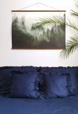 Elegancka oraz przytulna pościel z falbanką w odcieniu głębokiego granatu o rozmiarze 200x220 w jasnej skandynawskiej sypialni.