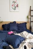 Poszewka z falbaną na poduszki o wymiarze 50x60 w głębokim odcieniu granatu.