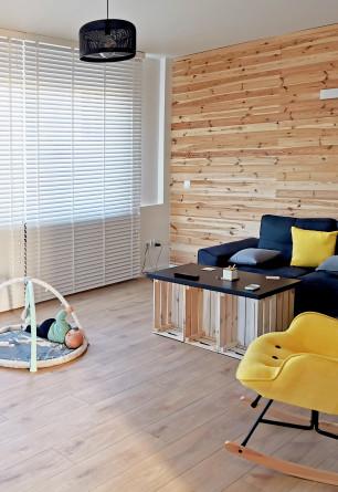 Biała żaluzja drewniana (CUKIER) o lamelkach 50mm z drabinką sznurkową montowana do sufitu nad oknem balkonowym w salonie.