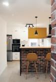 Musztardowa roleta rzymska w nowoczesnej kuchni z czerwoną cegłą. Montaż do sufitu nad wnęką.