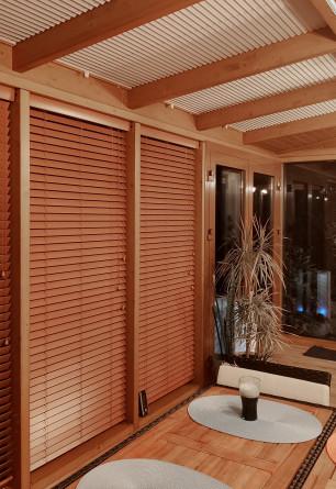 Żaluzja drewniana w kolorze szafran o lamelkach 50mm montowana we wnęce okiennej w przeszklonym patio.