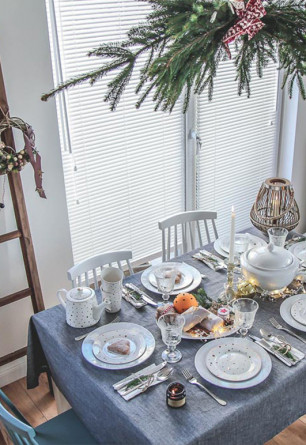 Biała drewniana żaluzja 25mm montowana bezinwazyjnie na oknie balkonowym w salonie. Styl skandynawski.