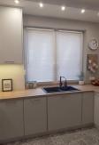 Biała żaluzja drewniana o lamelach 25mm montowana bezinwazyjnie na ramie okiennej w kuchni o stylu skandynawskim