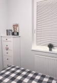Biała żaluzja drewniana o lamelach 25mm montowana do listw przyszybowych z prowadzeniem bocznym (żyłkowym) w sypialni.