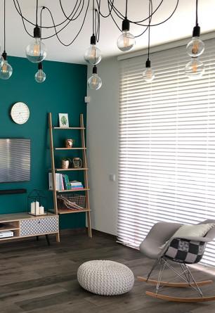 Biała drewniana żaluzja o lamelach 50mm na dużym balkonowym oknie w salonie