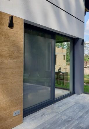 Aluminiowe drzwi moskitierowe przesuwne w kolorze antracyt na drzwiach tarasowych