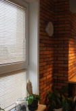 Żaluzje bambusowe 25mm w kolorze imbir (pobielane drewno) z widoczną i naturalną strukturą drewna na oknie w salonie.